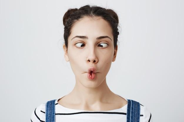 Mujer linda tonta hacer labios a pescado y entrecerrar los ojos, tontear