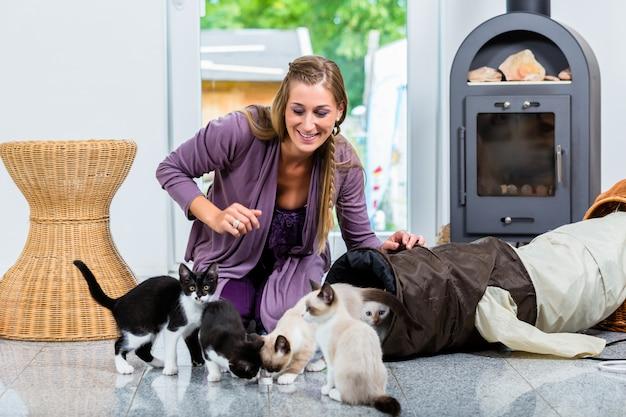Mujer con lindos gatitos y jugando tunel en piso.