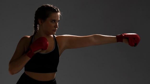 Mujer lista para golpear con guantes de box