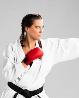 Mujer lista para luchar con guantes de box sobre fondo blanco.