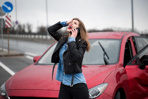 Mujer llama a un servicio de pie junto a un coche rojo