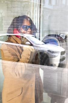 Mujer en una llamada en una cabina de teléfono de cristal con un reflejo de un coche en la calle