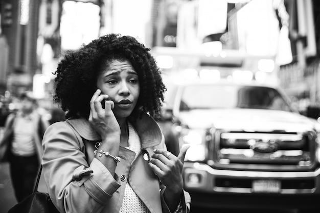 Mujer llamando al 911. mujer estadounidense en busca de emergencia después de un accidente automovilístico en manhattan