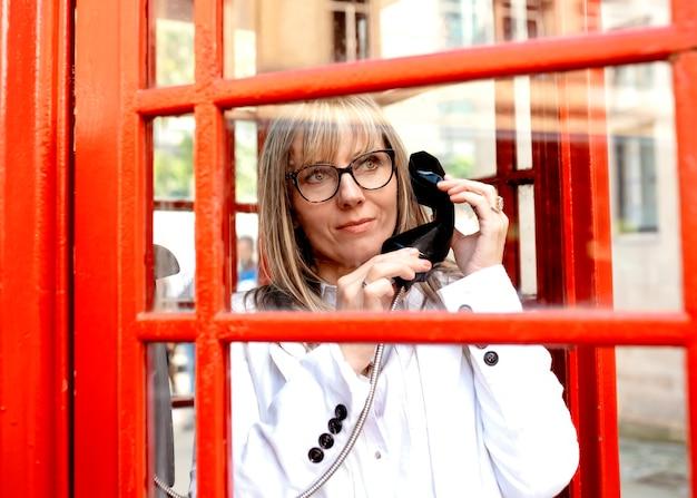 Una mujer llamando desde una cabina de teléfono roja en el centro de la ciudad.