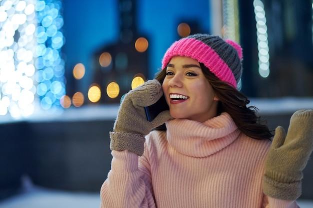Mujer llamando felicitar con navidad o año nuevo. mujer con smartphone en feria festiva