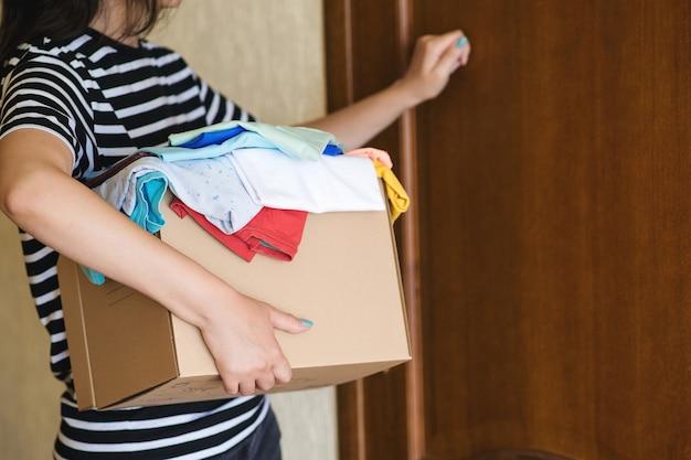 Mujer llamando a la puerta con caja de donación