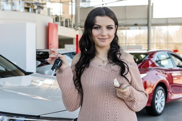Mujer con llaves y billetes en euros de pie cerca de coche nuevo