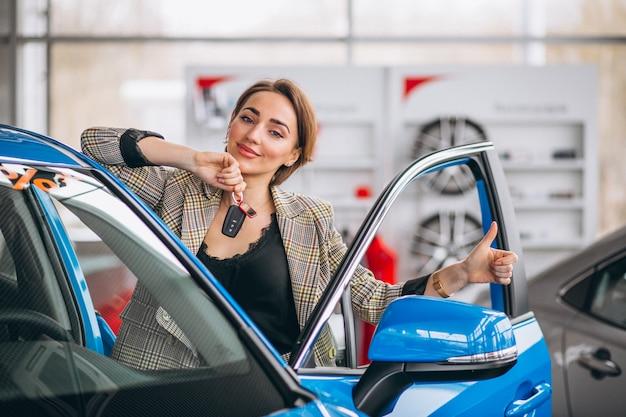 Mujer con llaves junto al coche.