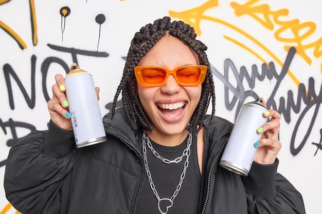 Una mujer llena de alegría tiene rastas se siente muy feliz dibuja graffitis con aerosoles se divierte pertenece a una pandilla de gamberros viste ropa de moda se ríe a carcajadas