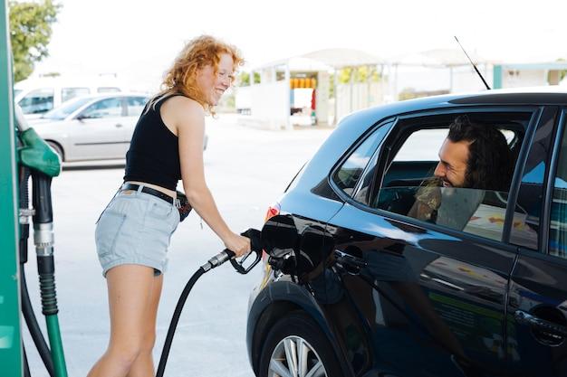 Mujer llenando el auto y sonriendo a un amigo en la estación de servicio