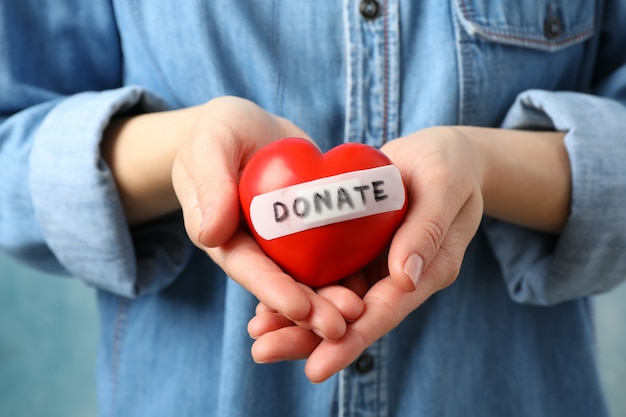 La mujer lleva a cabo el corazón en el espacio azul, cierre. cuidado de la salud, donación de órganos.