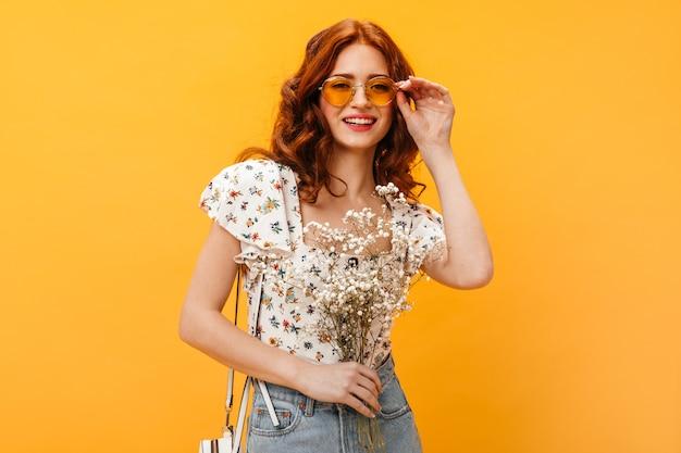 Mujer lleva gafas de sol. mujer bonita sonriendo y posando con ramo de flores blancas.