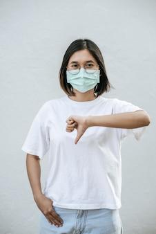 La mujer lleva una máscara y señala con el pulgar hacia abajo.