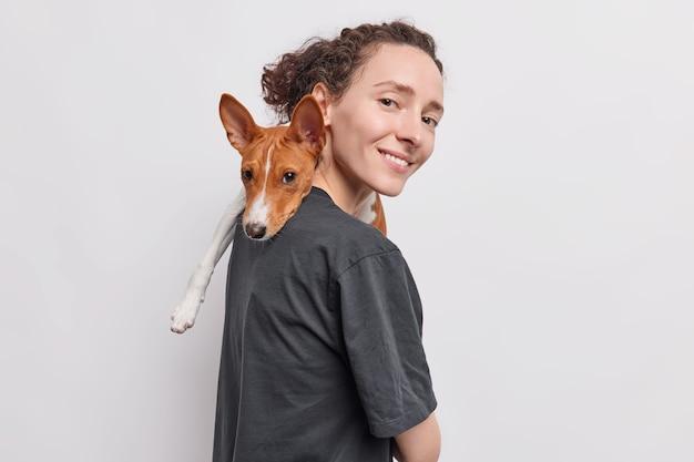 La mujer lleva el perro en el hombro juega con su mascota favorita expresa amor y cuidado se encuentra lateralmente aislado sobre blanco