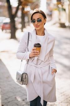 Mujer, llevando, abrigo, y, bebida, café