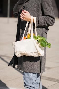 Mujer llevando bolsa con verduras orgánicas