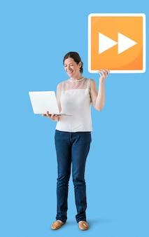 Mujer llevando un botón de avance rápido y una computadora portátil