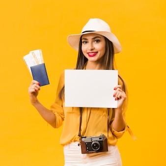 Mujer llevando una cámara y sosteniendo pasajes de avión y pasaporte