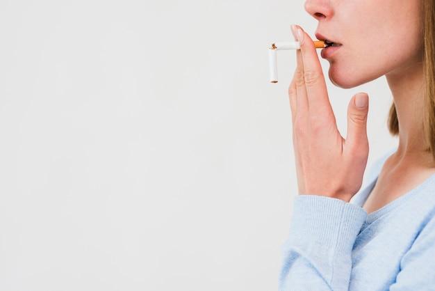 Mujer llevando cigarrillo roto sobre fondo blanco