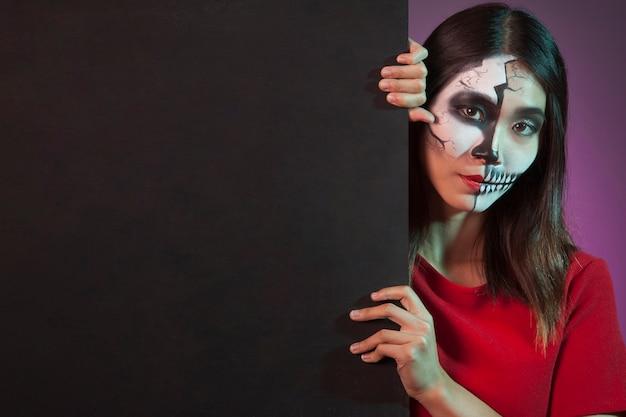 Mujer llevando disfraz de halloween detrás de pared