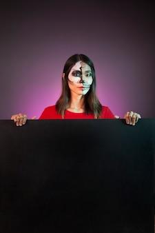 Mujer llevando disfraz de halloween detrás de tabla grande