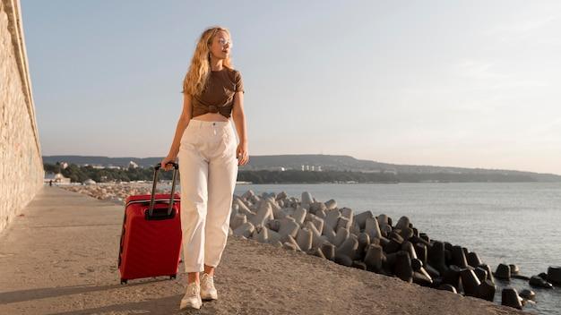 Mujer llevando equipaje de tiro completo