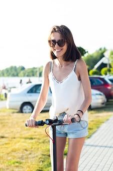 Mujer, llevando, gafas de sol, equitación, un, scooter