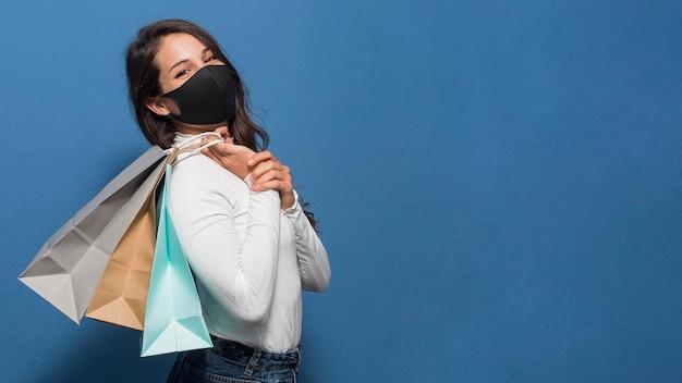 Mujer, llevando, máscara, y, tenencia, bolsas de compras