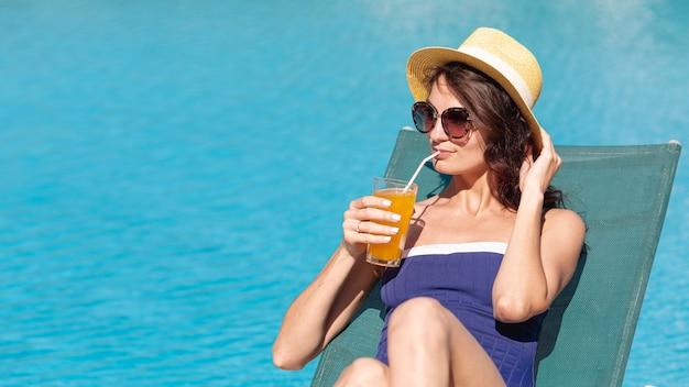 Mujer, llevando, sombrero, sentar cama solar