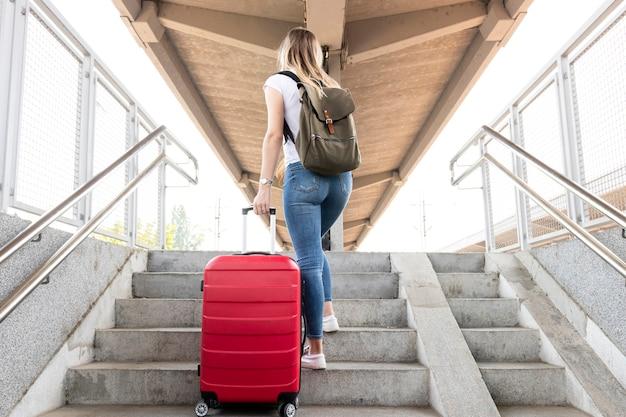 Mujer llevando su equipaje en las escaleras
