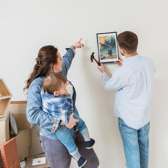 Mujer llevando a su hijo dirigiendo a su esposo para que arregle el marco en la pared
