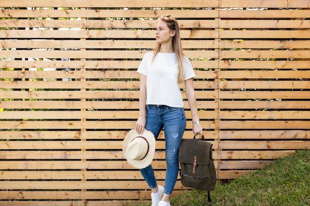 Mujer llevando su mochila y mirando a otro lado