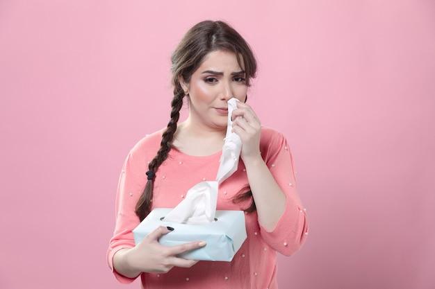 Mujer llorando con caja de servilletas