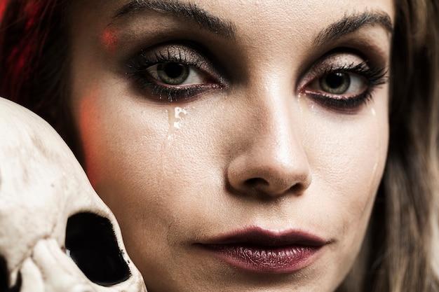 Mujer llorando con cráneo humano