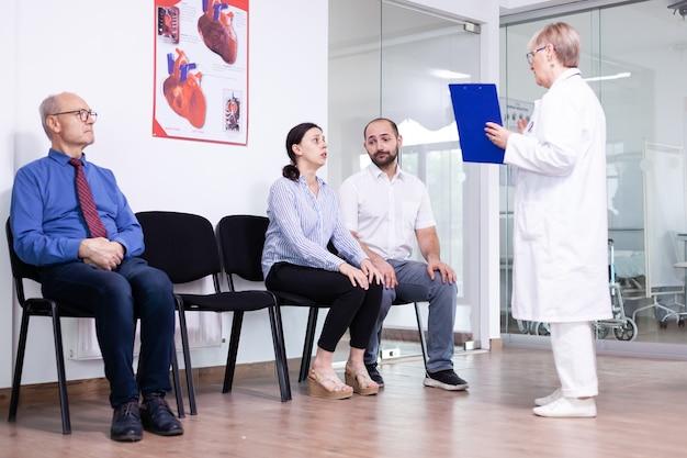 Mujer llorando mirando al médico después de noticias desfavorables en la sala de espera del hospital
