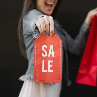 Mujer llorando con paquete de compra y signo de venta