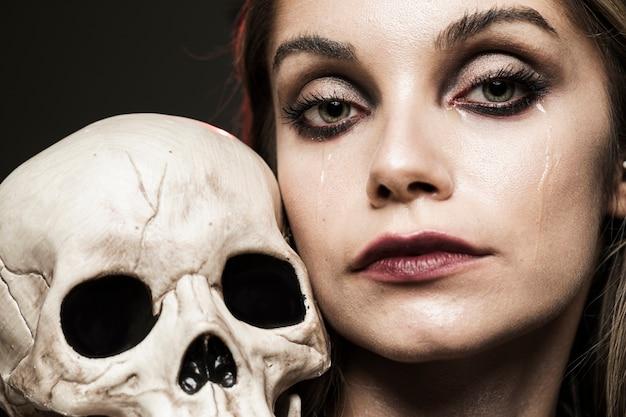 Mujer llorando sosteniendo cráneo humano