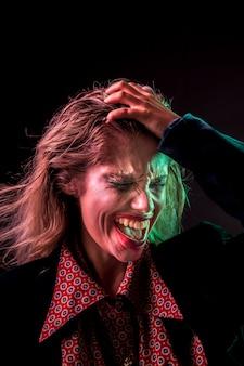 Mujer loca sosteniendo su cabeza con las manos para tomar fotos