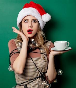 Mujer con luces de navidad y una taza de café en la pared verde