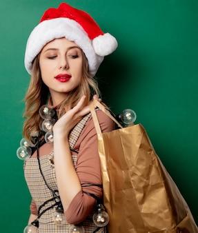Mujer con luces navideñas y bolso de compras