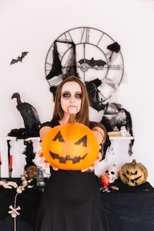 Mujer en lugar de halloween decorado con calabaza