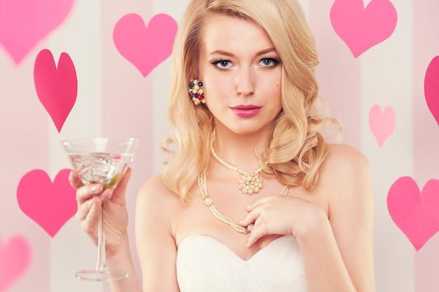 Mujer de lujo sexy sosteniendo un vaso con margarita
