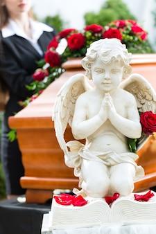 Mujer de luto en el funeral con rosa roja de pie en el ataúd o ataúd