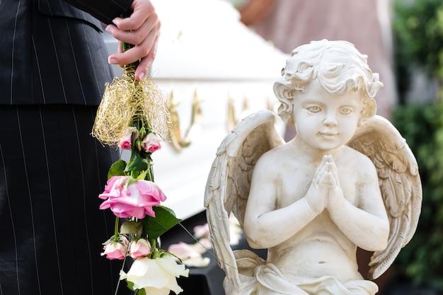 Mujer de luto en el funeral con rosa rosa de pie en el ataúd o ataúd