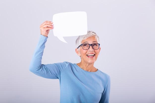 Mujer madura alegre con bocadillo de diálogo firme sobre su cabeza y sonriendo. feliz dama senior con burbuja de discurso