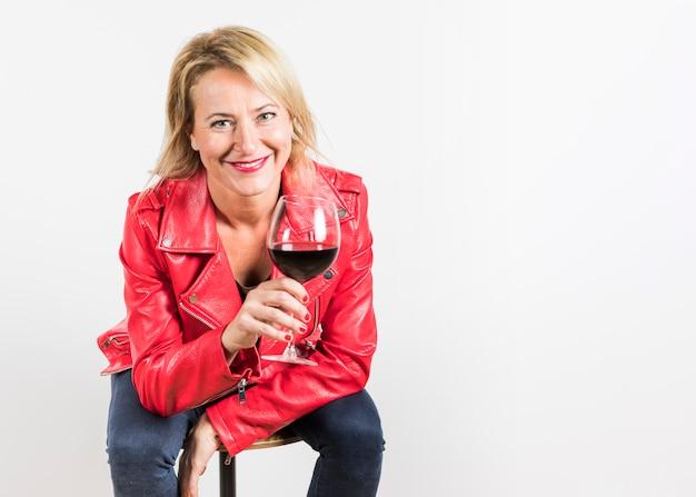 Mujer madura alegre que se sienta en el taburete que sostiene la copa de vino a disposición aislada en el fondo blanco