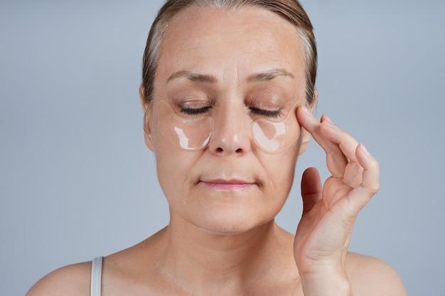Mujer madura aplicando parches debajo de los ojos. cuidado de la piel facial en la vejez.
