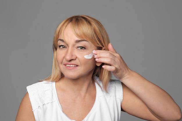 Mujer madura, aplicar crema facial contra gris