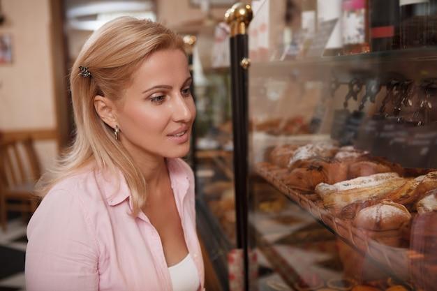 Mujer madura atractiva examinar escaparate en la panadería