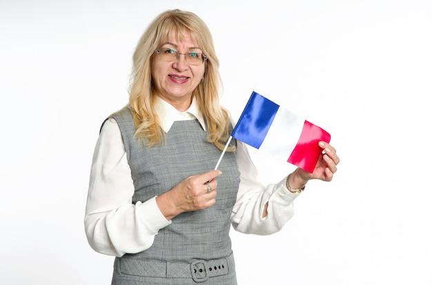 Mujer madura con la bandera de francia sobre fondo claro.